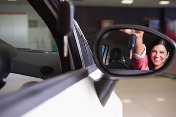 Woman showing car key in rear view mirror