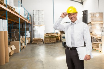 Warehouse manager wearing hard hat holding clipboard
