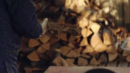 Man chopping firewood with circular saw. Slow motion