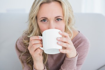Pretty blonde on couch drinking hot drink