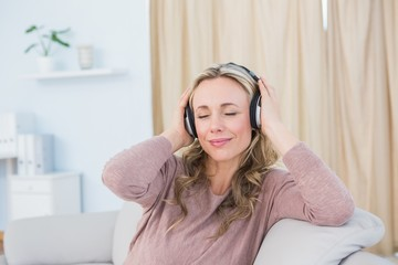 Smiling blonde on couch listening music with headphones