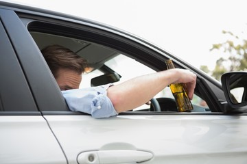 Man drinking beer while driving