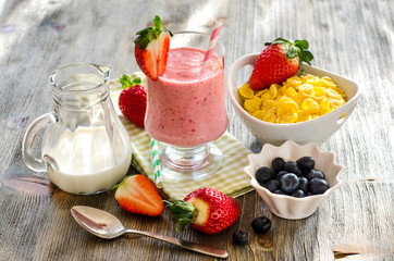 Healthy morning meal with cornflakes, strawberry smoothie and be