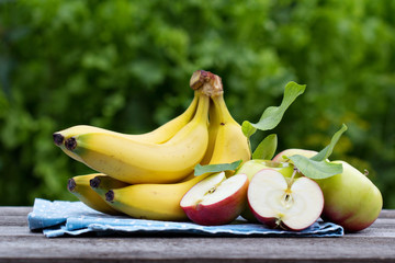 Ripe bananas and apples on the wooden table