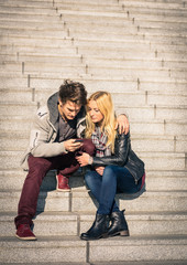 Hipster couple in love having fun with smartphone in urban area