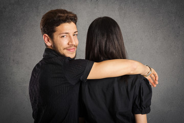 Casual couple studio portrait from behind, man looking at camera