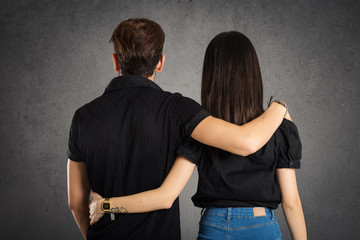 Casual couple studio portrait from behind against grunge backgro