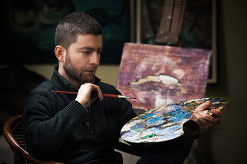 Portrait of young artist holding art palette