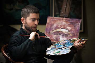 Portrait of young artist holding art palette