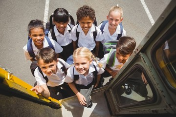 Cute schoolchildren getting on school bus