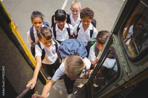canvas print picture Cute schoolchildren getting on school bus
