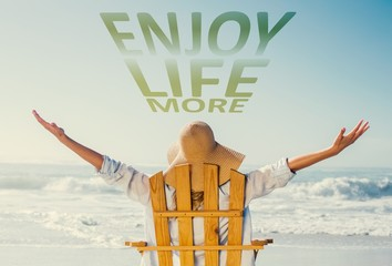 Composite image of woman relaxing in deck chair by the sea