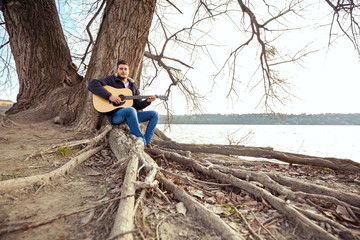 Young man sitting on a tree playing guitar and singing