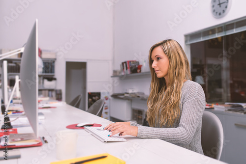 canvas print picture Young woman portrait working with computer in modern office.