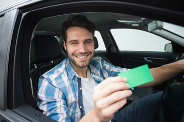 Young man smiling at camera showing card
