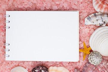 notebook over pink bath salt and seashells background
