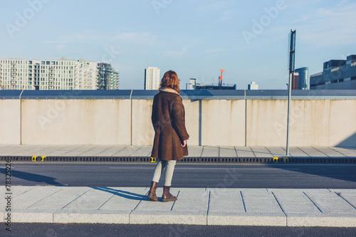 Fototapeta Woman looking at skyline of city in winter