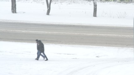 Two unidentifiable men walking along the road in snow