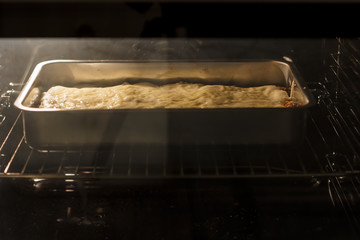 Lasagna in a metal container is cooking in oven