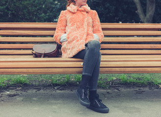 Woman in fur coat sitting on bench