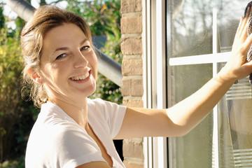 Frau hat Freude bei Fensterputzen und Hausarbeit
