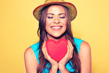 Young woman portrait with closed eyes holding red Heart.