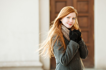 Young redhead woman wearing coat and scarf posing outdoors