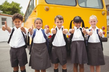 Cute schoolchildren smiling at camera by the school bus