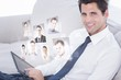 Composite image of smiling businessman using digital tablet