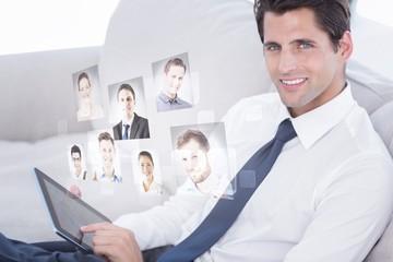 Composite image of smiling businessman using digital tablet
