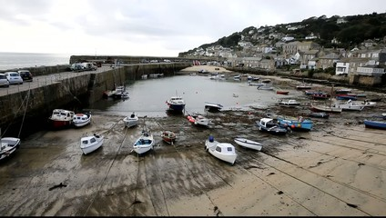 Low tide boats in Mousehole harbour Cornwall UK