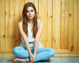 Girl sitting on a floor with crossed legs.