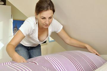 Hausfrau macht Bett mit frischer Bettwäsche