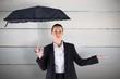 Composite image of businesswoman holding a black umbrella