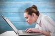 Composite image of attentive businesswoman typing on laptop
