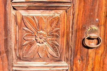 Old carved door with metal handle