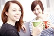 Two happy female friends with coffee cups