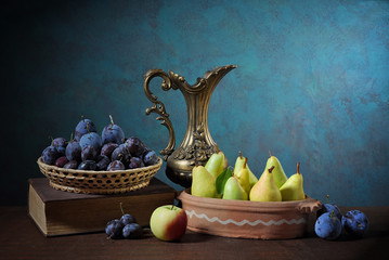 Pears, plums, books and a metal carafe