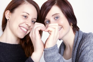 two girls friends make a heart with hands