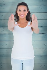 Composite image of pretty brunette presenting with hands