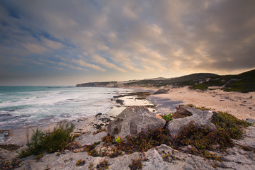 Late evening landscape of ocean over rocky shore heavy clouds bl