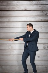Composite image of young businessman pulling a rope
