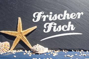 Schiefertafel mit Seestern und Muscheln mit Frischer Fisch