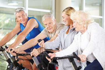 Trainerin mit Stoppuhr zwischen Senioren beim Spinning