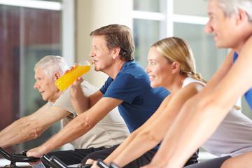 Mann trinkt Orangensaft im Fitnesscenter