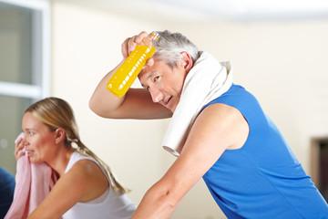 Erschöpfter Mann schwitzt im Fitnesscenter
