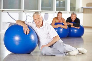 Alter Mann mit Gymnastikball im Rehazentrum