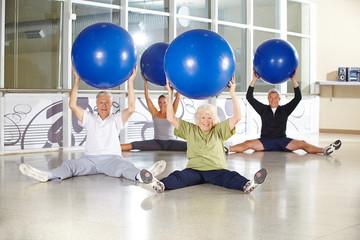 Gruppe Senioren mit Gymnastikball beim Rückentraining