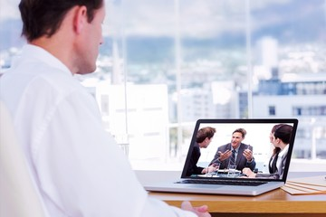 Composite image of businessman looking at a laptop