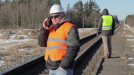 Railway engineer talking on the cell phone near the railway